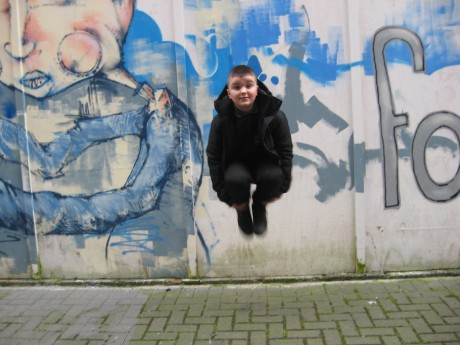 Boy jumping next to graffiti'd wall