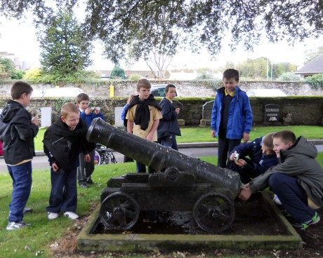 Children inspecting a cannon in graveyard