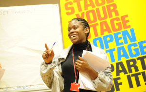 Image of smiling black woman with papers explaining something in front of a banner which reads 'Your Open Stage'
