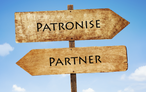 Signposts pointing to 'patronise' and 'partner'