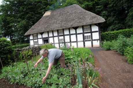 Person gardening in front of a museum-cottage