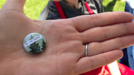 Hand holding badge which reads ''be the change' courtesy of Santa Cruz Museum of Art and History