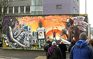 people outside viewing graffiti